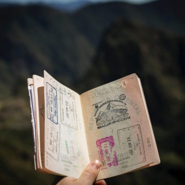 A hand in open air holds an old open passport.